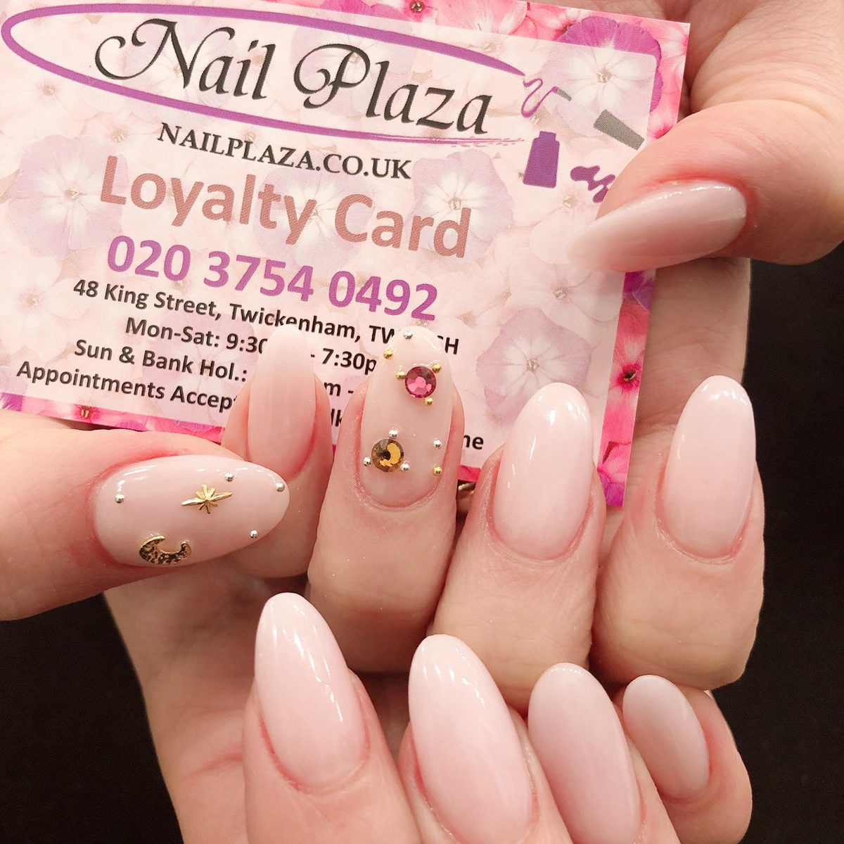 oval shaped nail extension in pale pink with 3D designs